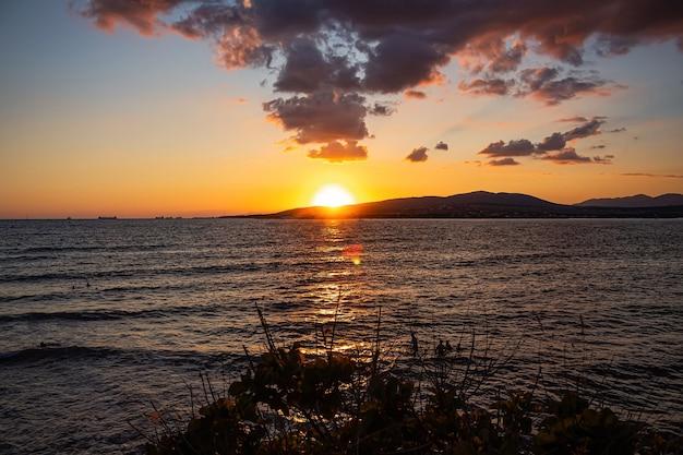 Een heldere zonsondergang op zee verlaat soepel de baai en de bergen van de badplaats gelendzhik kleurrijk zomerlandschap en vakantie aan de kust van de zwarte zee