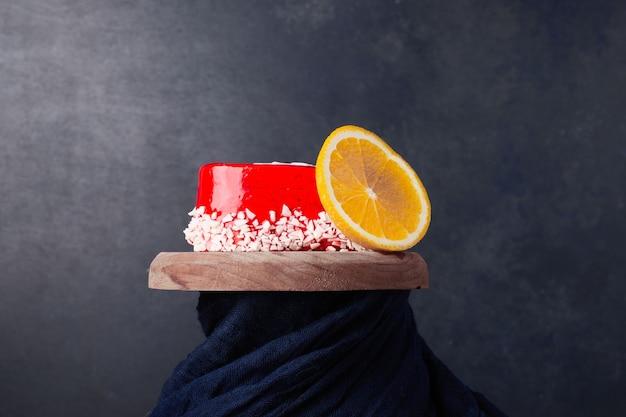 Een hele cake met rode gelei en een schijfje sinaasappel
