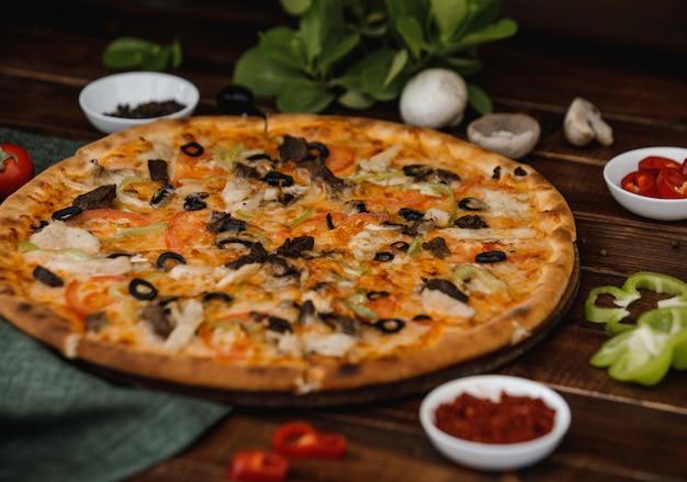 Een hele gemengde olijfpizza geserveerd op een houten bord met kruiden.