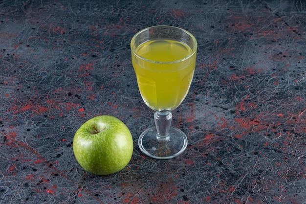 Een hele groene appelfruit met een glazen kopje sap op stenen tafel.
