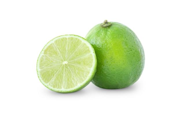 Een hele groene limoen en de helft geïsoleerd op een witte achtergrond
