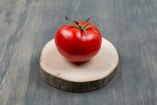 Een hele sappige tomaat op een houten tafel