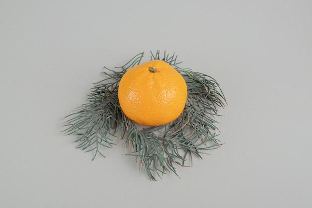 Een hele verse mandarijn op een grijze achtergrond.
