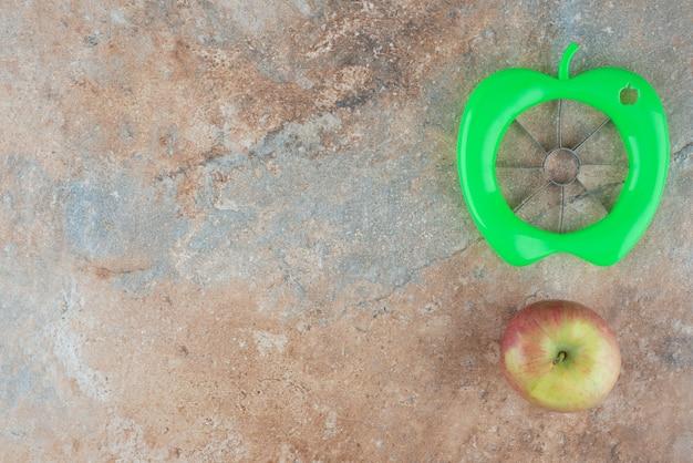 Een hele zoete appel met schilgereedschap op marmeren tafel.