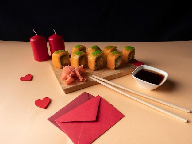 Een heleboel gele sushi op een bord en twee rode kaarsen en twee rode enveloppen staan ernaast op een gele achtergrond
