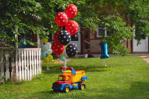 Een heleboel heliumballonnen zijn vastgebonden aan een grote speelgoedauto. verjaardagsfeest.