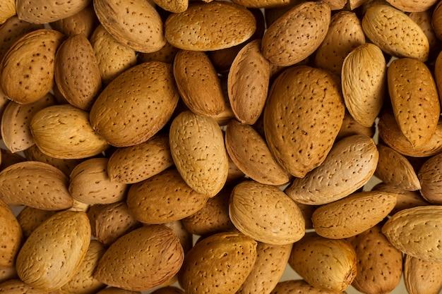 Een heleboel noten close-up. ongepelde amandelen. natuurlijke achtergrond voor gezond eten concept