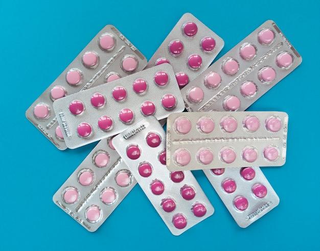Een heleboel roze pillen in blaren op een blauwe achtergrond. medisch concept.