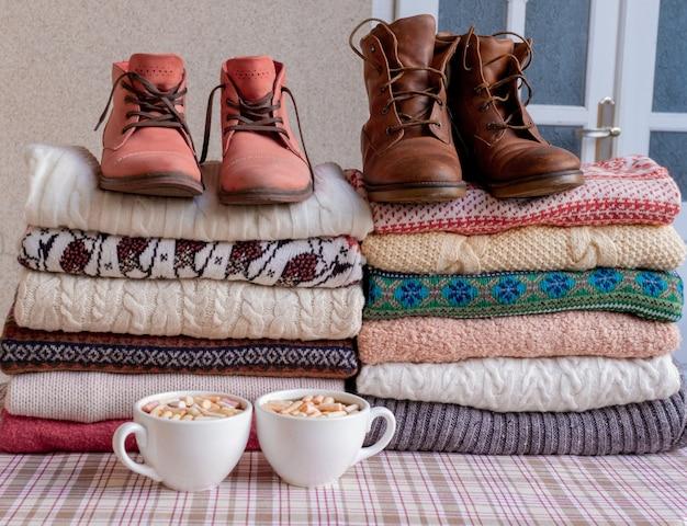 Een heleboel truien en pullovers verschillende kleuren gevouwen in twee stapels met bruine en rode schoenen en kopjes koffie.