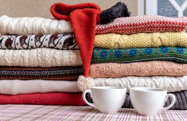 Een heleboel truien en pullovers verschillende kleuren gevouwen in twee stapels op de tafel met twee kopjes koffie.
