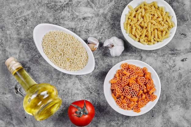 Een heleboel verschillende gevormde ongekookte pastakommen op marmeren tafel met olie, knoflook en tomaat.