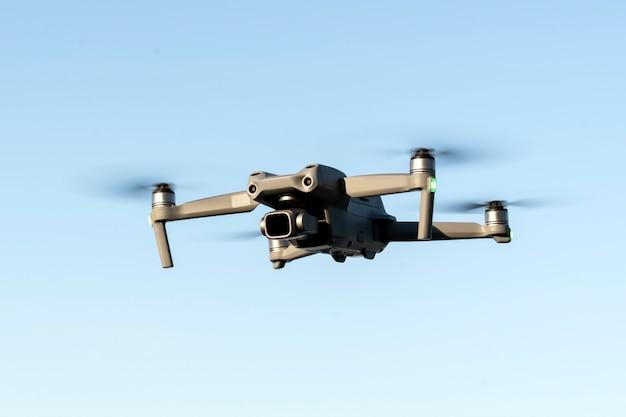 Een helikopter tijdens de vlucht in close-up tegen de achtergrond van een heldere blauwe lucht een apparaat voor het maken van video's ...