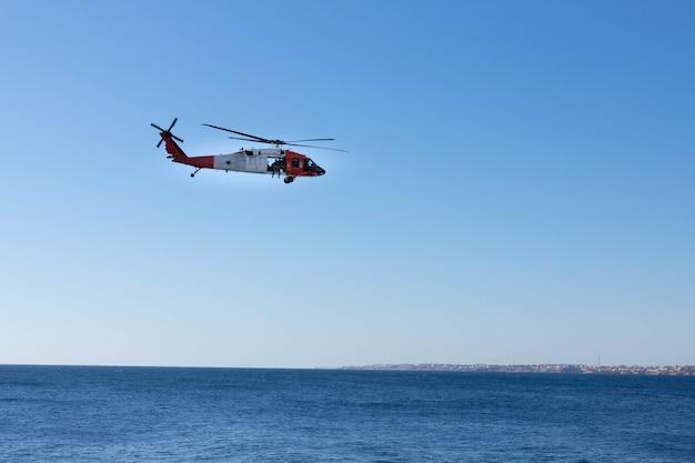 Een helikopter van de kustwacht met soldaten vliegt over de kust van de rode zee.