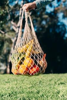 Een herbruikbare boodschappentas van mesh katoen vol groenten en fruit.
