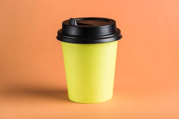Een herbruikbare koffiekop van groen papier met een gesloten zwart deksel.