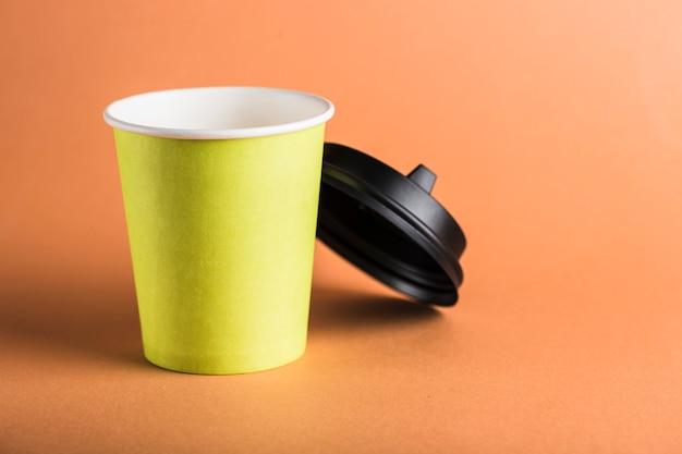 Een herbruikbare koffiekop van groen papier met een open zwart deksel.