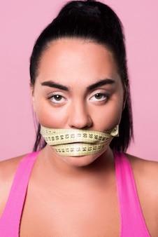 Een hint laten vallen. close-up portretten van uitgehongerde mulat vrouw met bedekte mond door meetlint