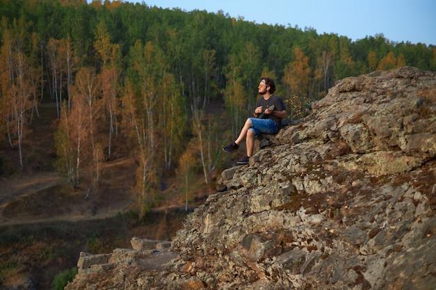 Een hippie-man met bril en spijkerbroek speelt de ukelele die op de top van een klif in het midden van... Premium Foto