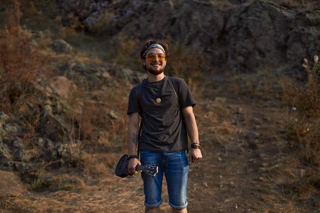 Een hippie-man met zonnebril staat op een open plek bij de rotsen glimlachend en recht in de...