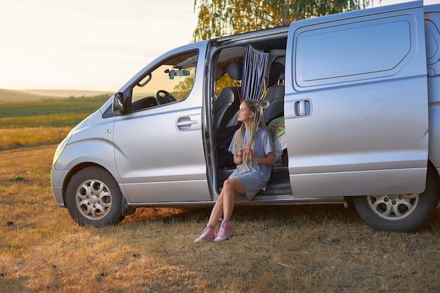Een hippiemeisje zit in een zilveren minibusje op een veld tegen de achtergrond van bergen, het concept van f...