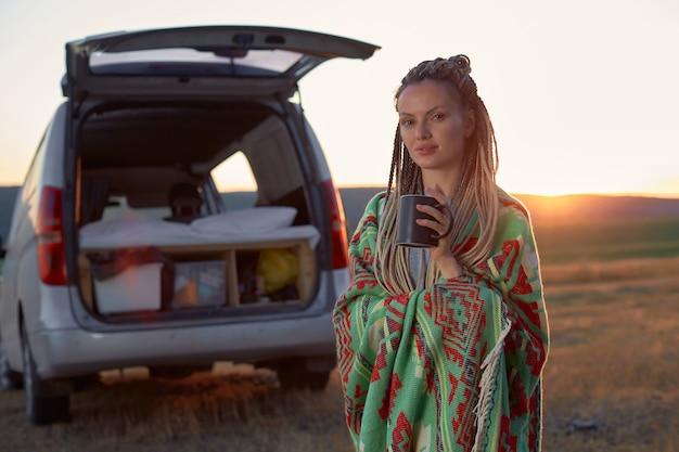 Een hippievrouw in een heldere etnische deken houdt een mok in een veld bij zonsondergang in de buurt van haar autohig...