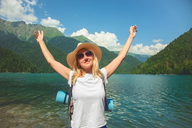 Een hipster meisje in een hoed reist in de bergen. het meisje houdt van reizen.