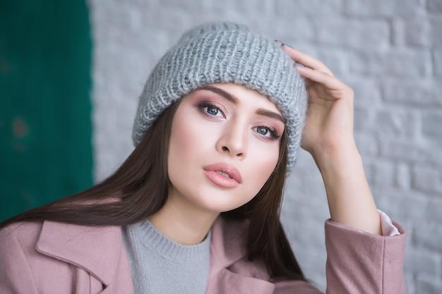 Een hipstermeisje met lang bruin haar, gekleed in een stijlvolle jas en gebreide muts, kijkt opzij terwijl ze op een lichte witte bakstenen achtergrond op straat staat. horizontale mock-up.