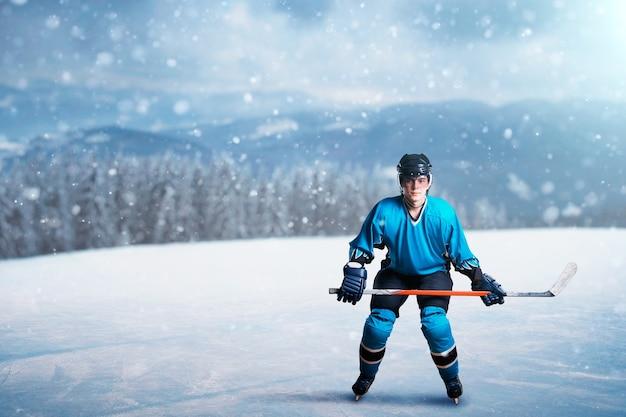 Een hockeyspeler met stok op open ijs, spelconcept, besneeuwd bos. mannelijke persoon in helm, handschoenen en in beschermend uniform buitenshuis, wintersportspel