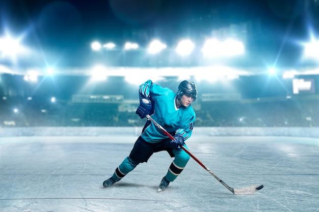 Een hockeyspeler schaatsen met stok op ijs arena, schijnwerpers op achtergrond. mannelijke persoon in helm, handschoenen en uniform speelspel