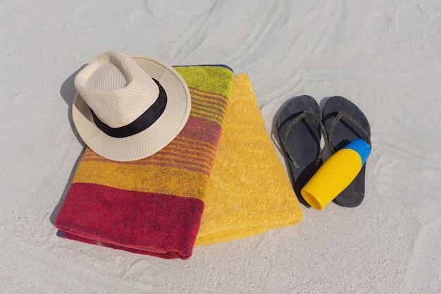 Een hoed, lotionfles, slippers en handdoeken liggen op het zand.