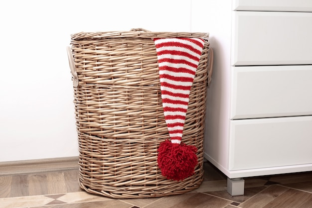 Een hoed met rode en witte strepen met een grote rode pompon die aan een rieten mand hangt naast een witte muur en wit meubilair.