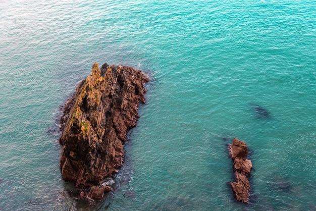 Een hoge hoekmening van rotsen in een zee onder het zonlicht in ierland