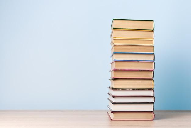 Een hoge stapel boeken staat op een houten tafel tegen een lichtblauwe muur