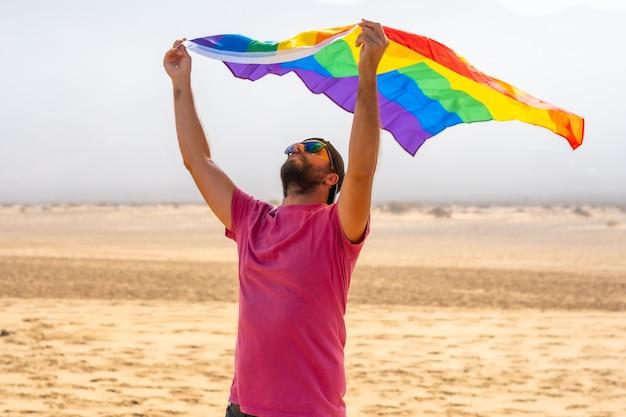 Een homo met de lgbt-vlag die ervan geniet om met de wind in een woestijn te bewegen, symbool van homoseksualiteit, regenboogvlag