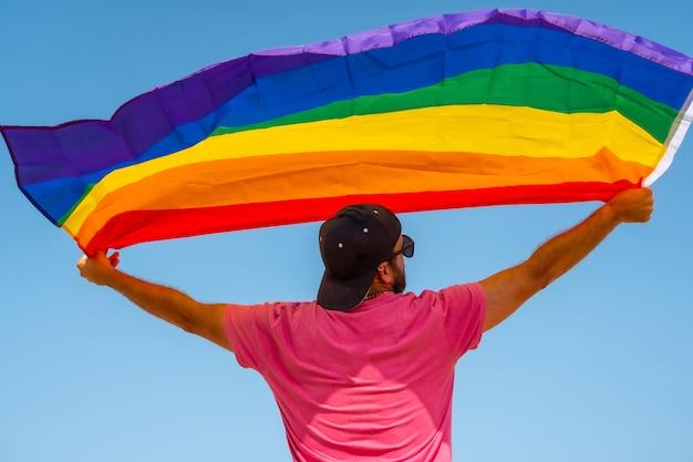 Een homo met de lgbt-vlag op zijn rug die beweegt met de wind met de lucht op de achtergrond, symbool van homoseksualiteit, regenboogvlag