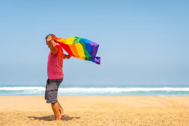 Een homo met een roze t-shirt en zwarte pet met de lgbt-vlag op een strand, symbool van homoseksualiteit
