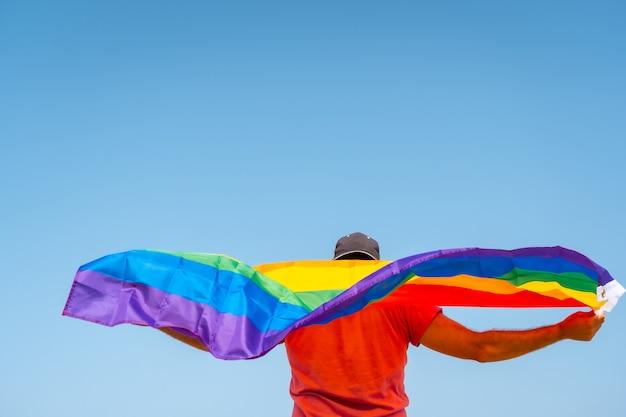 Een homo met een roze t-shirt en zwarte pet met de lgbt-vlag op zijn rug die beweegt met de wind met de lucht op de achtergrond, een symbool van homoseksualiteit
