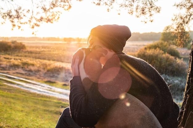 Een hond knuffelen in de prachtige natuur bij zonsondergang. vrouw die avondzon onder ogen ziet zit met haar huisdier naast haar en geniet van schoonheid van aard