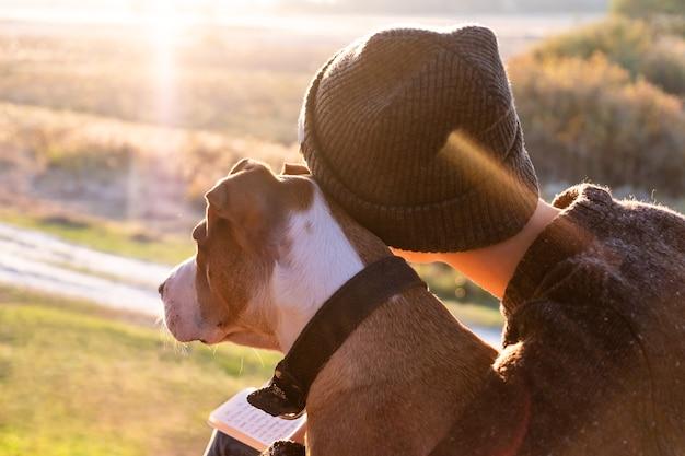 Een hond knuffelen in de prachtige natuur bij zonsondergang. vrouw die avondzon onder ogen ziet zit met haar huisdier naast haar