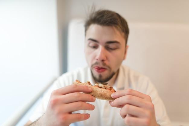 Een hongerige man kijkt nauwkeurig naar een stuk pizza in zijn hand en staat op het punt het op te eten