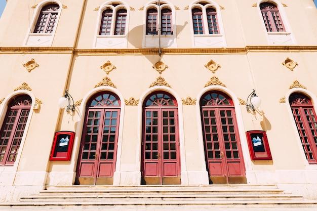 Een hoog gebouw met drie rode deuren in ovale openingen op een lichte muur met lijstwerk en patronen