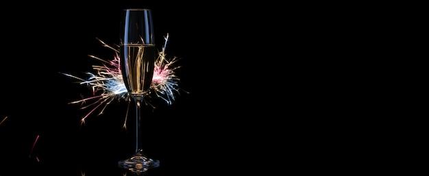Een hoog glas met champagne in het licht van bengalen lichten
