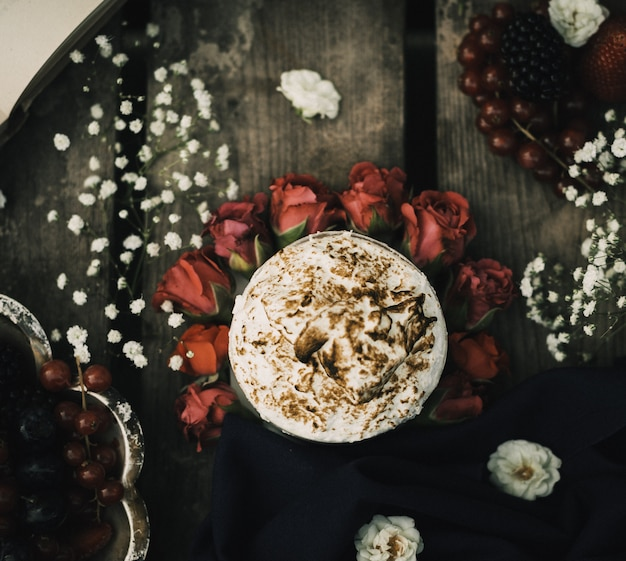 Een hoogste dichte omhooggaande hete koffie lekker op de rode rozen en de bruine houten rustieke oppervlakte