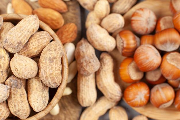 Een hoop amandelen, pinda's en hazelnoten in kommen en op een houten bord. hoge kwaliteit foto