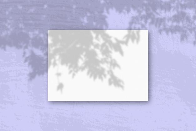 Een horizontaal a4-vel wit geweven papier op de blauwe muur