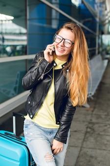 Een horizontaal portret van mooi meisje met lang haar dat zich buiten op de luchthaven bevindt. ze draagt een gele trui, een zwarte jas en een spijkerbroek. ze praat aan de telefoon en lacht naar de camera.