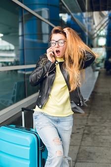 Een horizontaal portret van mooi meisje met lang haar in glazen die zich dichtbij koffer buiten in luchthaven bevinden. ze draagt een gele trui, een zwarte jas en een spijkerbroek. ze ziet er raar uit.