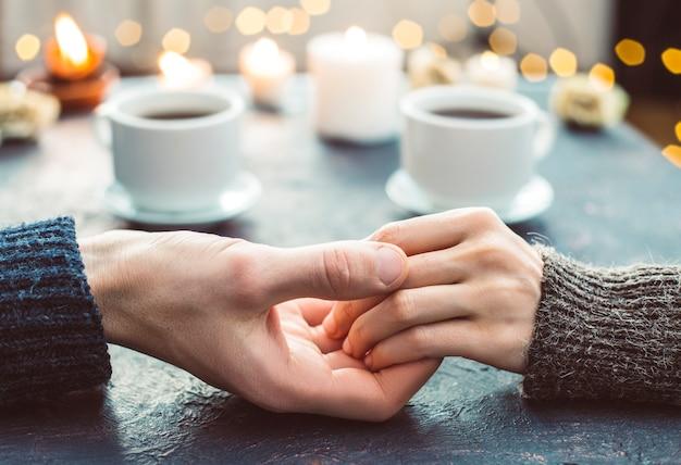 Een houdend van paar houdt handen bij een romantisch diner in restaurant met kaarsen.