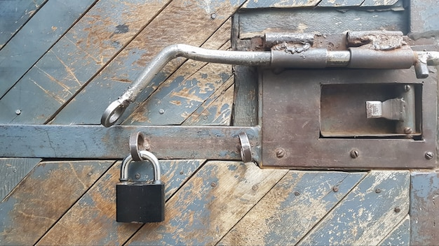 Een hout verweerde, textuur plank deur met een hangslot, klink en metalen beslag.