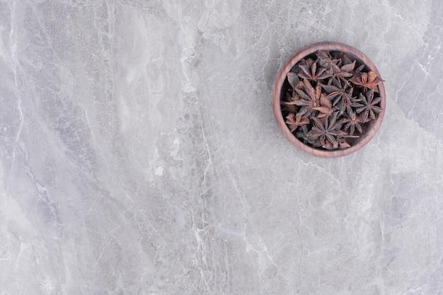 Een houten beker vol anijsbloemen op het marmer
